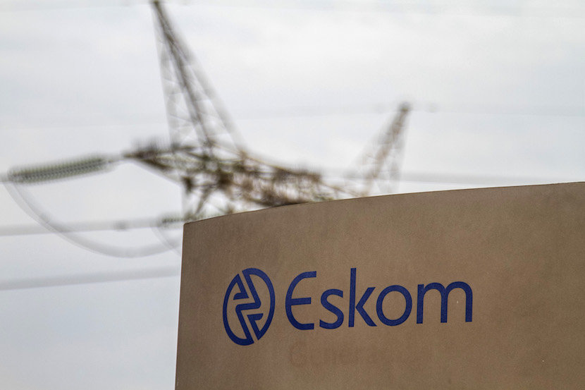 An electricity pylon stands beyond an Eskom sign at the entrance to the Grootvlei power station, operated by Eskom Holdings SOC Ltd., in Grootvlei, South Africa, on Monday, Nov. 3, 2014. Eskom said South Africa's power supply remains strained as it investigates what caused a silo storing coal to collapse, forcing the state-owned utility to cut electricity to customers.