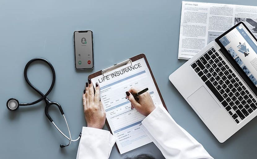 Person Holding Pen and Life Insurance Paper Beside Macbook Pro